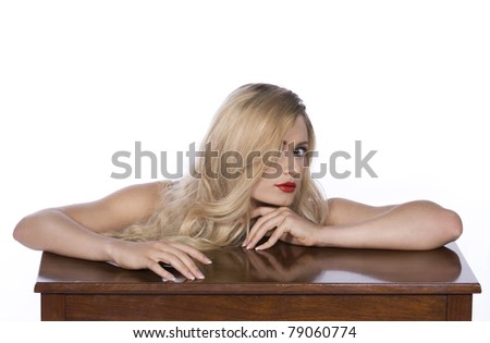 Blond fashion model leaning on table