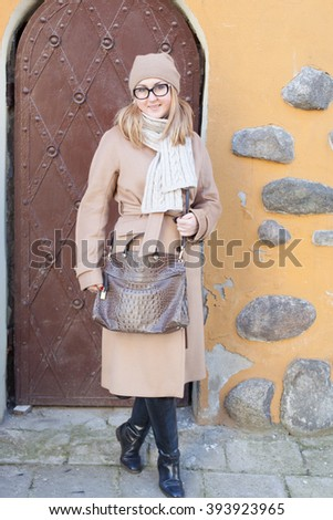 Blond fashion woman walking outdoor in the old town of Warsaw. Wearing elegant camel coat and glasses. - stock photo