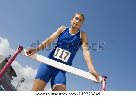 Blond female athlete with hurdle