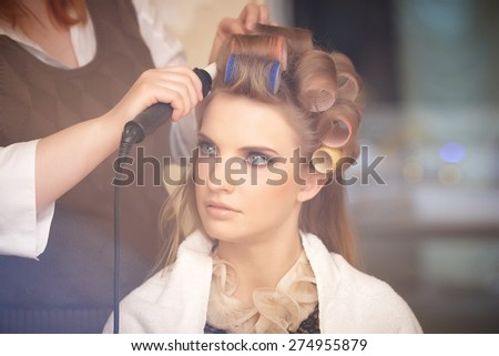 Blond female in hair salon. Hairdresser on background