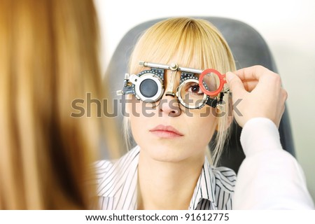 Blond female patient on medical attendance at the optometrist, wearing trial frame for eye testing - stock photo