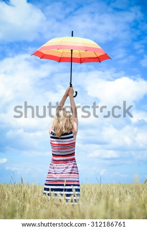 Blond female rising umbrella and standing in golden wheat field. Backview of woman in striped dress who looking into the distance over blue sky background - stock photo