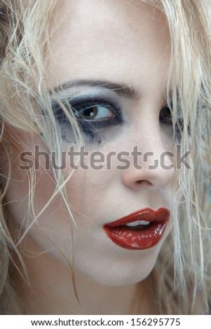 Blond female witch with strange makeup. Studio photo