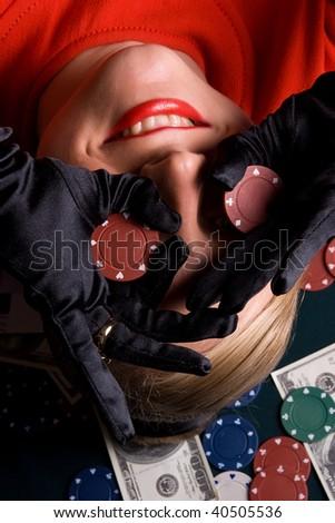 Blond gambler having fun with poker chips - stock photo