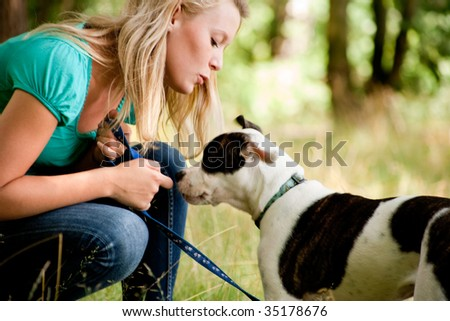 Blond girl and a American bulldog in the park - stock photo