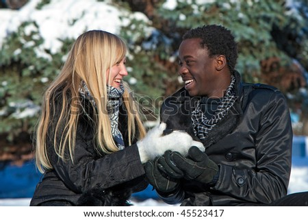 Blond girl and dark-skinned boy are having a tea in the winter forest