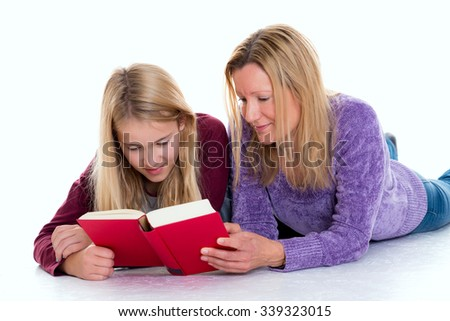 blond girl and her mother lying on the floor and reading a book