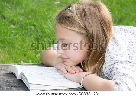 Blond girl at park with book on wooden bench