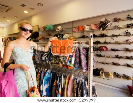 Blond girl buying clothes in a shop - stock photo