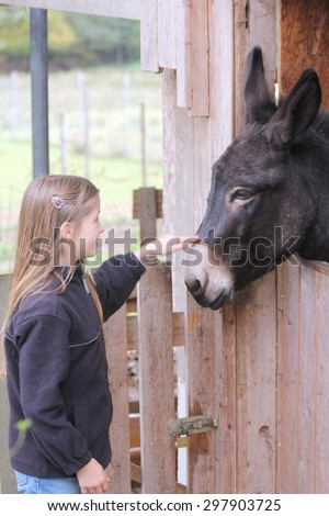 Blond girl cuddling a black donkey