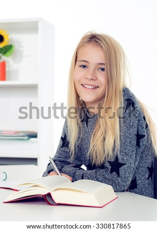 blond girl doing homework in his room