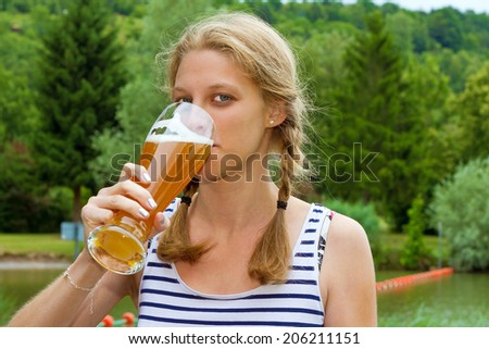 Blond girl drinking wheat beer - stock photo
