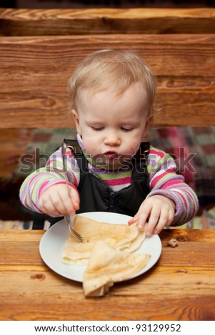Blond girl eating delicious pancakes on white plate - stock photo