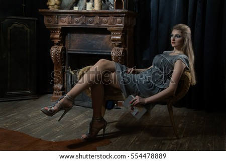 Blond girl in a gray dress with a book sitting on the ottoman