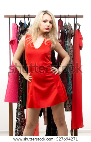 blond girl in a red dress. front of clothes hanger.