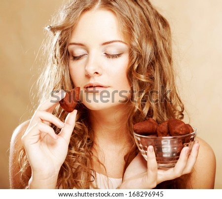 blond girl in act to eat a chocolate candy - stock photo