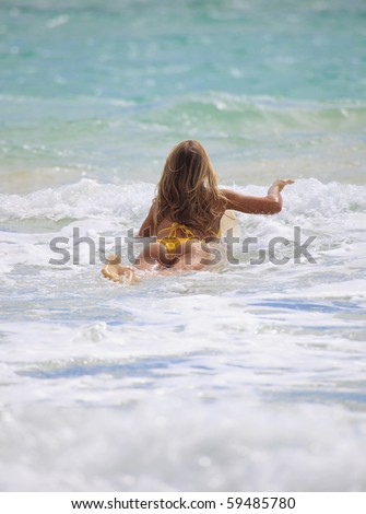 blond girl in bikini paddles her surf board towards the waves - stock photo