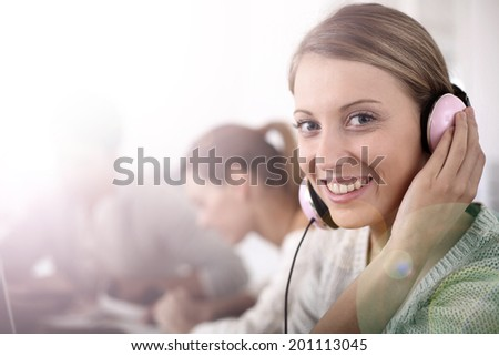Blond girl in class with music headphones on