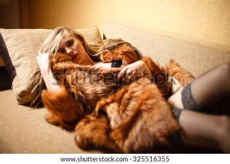 Blond girl in fur and lingerie on sofa. - stock photo