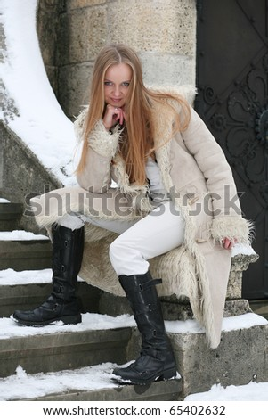 Blond girl in fur coat sitting on the balustrade - stock photo