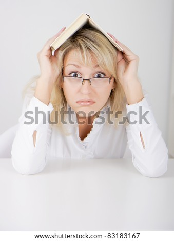 blond girl in glasses hidden under a book - stock photo
