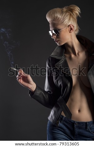 Blond girl in leather jacket and jeans with sunglasses and cigarette - stock photo