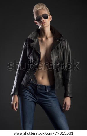 Blond girl in leather jacket and jeans with sunglasses smoking cigarette - stock photo