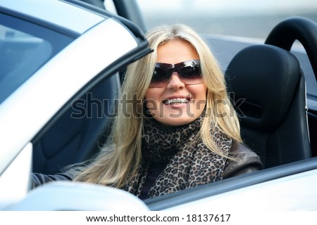 Blond girl in sunglasses driving convertable car - stock photo