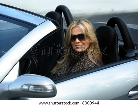 Blond girl in sunglasses driving convertible car
