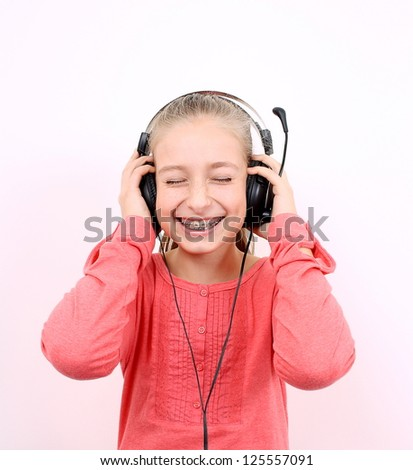 Blond girl listens to music with headset and laughs