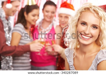 Blond girl looking at camera with toothy smile on background of toasting friends - stock photo