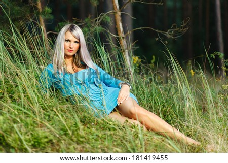 Blond girl lying on the grass in the forest. - stock photo