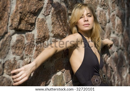 blond girl near stone wall