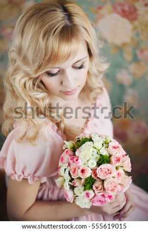 blond girl on a floral background holding in your hands a bouquet