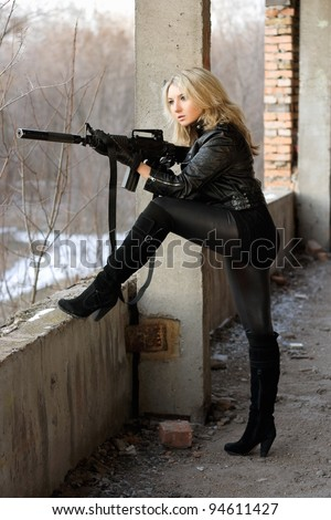Blond girl on high heels taking a shot with machine gun - stock photo