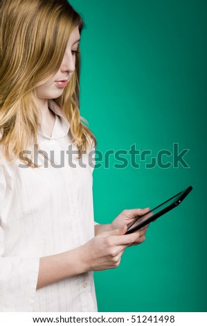 blond girl reading electronic books on an ebook reader device - stock photo