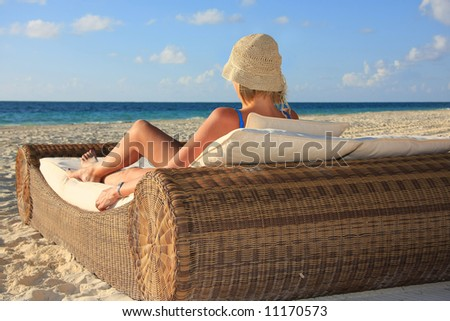 Blond girl relaxing on beach bed. - stock photo