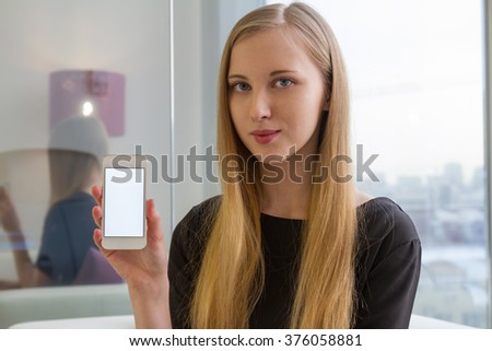 Blond girl show phone white display and smiling in office glass