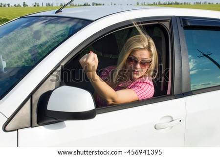 Blond girl shows her fist in the car