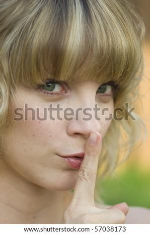"Blond girl signaling ""quiet"" - stock photo"
