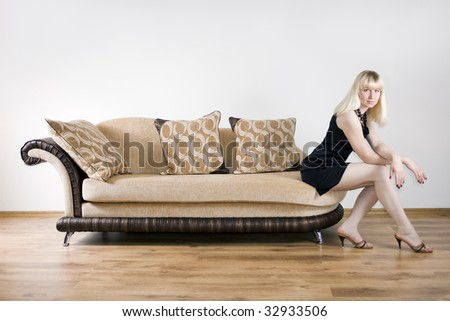 Blond girl sits on the sofa against the background of the white wall - stock photo