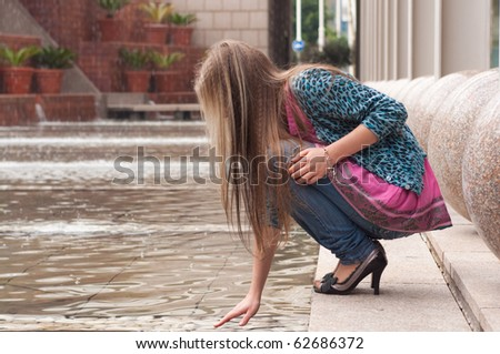 Blond girl sitting at fountain and touching water - stock photo