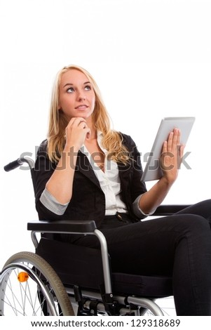Blond girl sitting in a wheel chair with tablet PC - stock photo