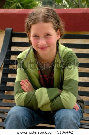 Blond girl sitting on a park bench