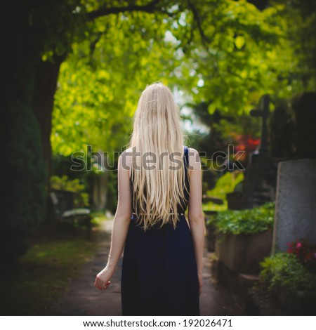 Blond girl walking alone at cemetery. Selective focus  - stock photo