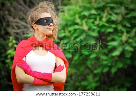 Blond girl wearing a red superhero uniform and a black mask smiling