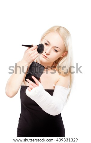 Blond girl with a broken arm in plaster having trouble putting a lipstick - stock photo