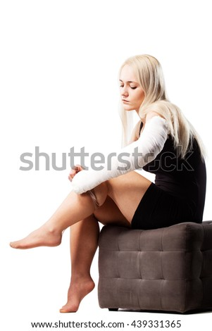 Blond girl with a broken arm in plaster, trying to put on stockings - stock photo