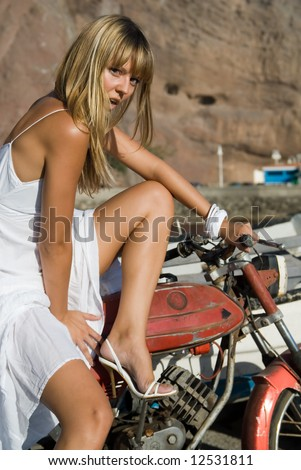 Blond girl with a motocycle in the harbor - stock photo