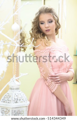 Blond girl with beautiful hair, wavy hair and a pink dress posing in the studio.